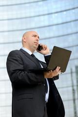 Uomo d'affari al telefono con computer portatile