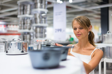 Pretty, young woman choosing a the right pot for her cooking