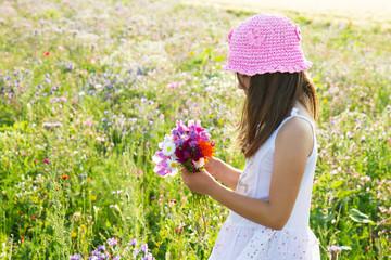 bimba a racogliere i fiori