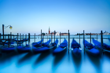 Venice, gondolas on sunset and church on background. Italy
