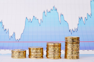 Uptrend stacks of golden coins and  financial  chart as backgrou