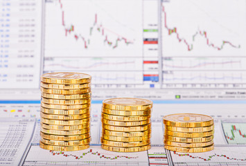 Down trend stacks of golden coins and financial chart as the bac