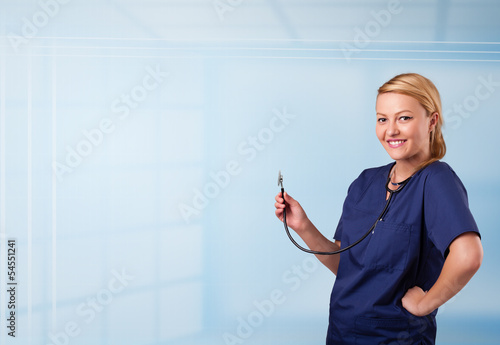 Pretty nurse in hospital listening to empty copy space with sthe