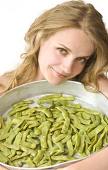 beautiful blonde woman holding a bowl with fresh green peas