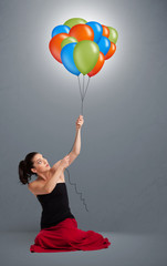 Young woman holding colorful balloons