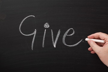 Hand writing the word Give on a Blackboard