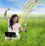 Beautiful female listening to music on laptop - outdoor
