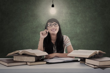 Beautiful student under light bulb and books in class