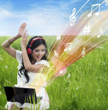Excited female download music from laptop - outdoor