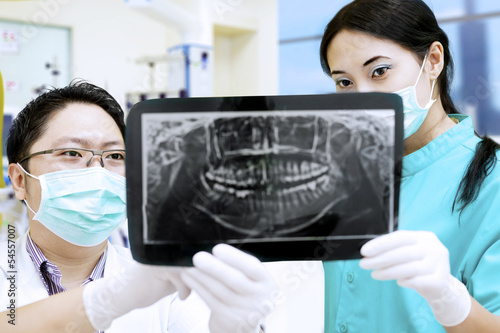 Attractive assistant and dentist looking at x-ray at hospital
