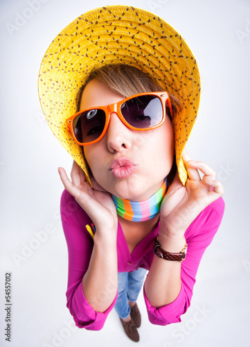 pretty girl with yellow summer hat giving a kiss