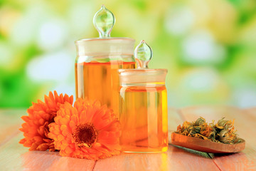 Medicine bottles and calendula flowers on wooden table