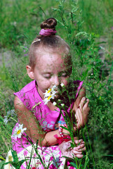 A child smelling wild flowers with closed eyes