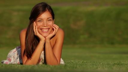 Young beautiful woman smiling lying in grass