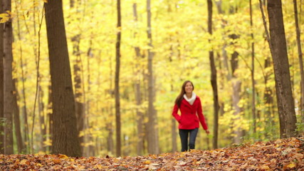 Autumn woman walking in fall forest