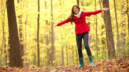Girl playing in autumn forest throwing leaves