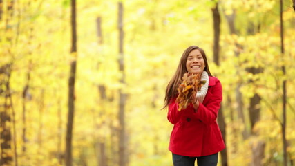 Happy girl playing in autumn leaves, fall forest