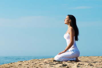 Woman in white clothes meditating on beach, portrait in profile