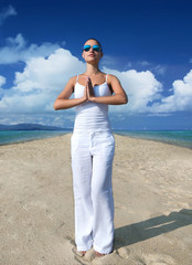 Young woman in white clothes meditating on the beach