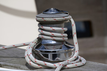 Winch of a sailboat and white rope
