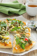 Pizza with arugula, zucchini and capers.