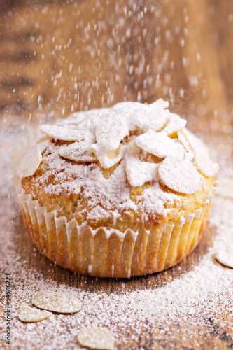 Almond muffins being sprinkled with sugar