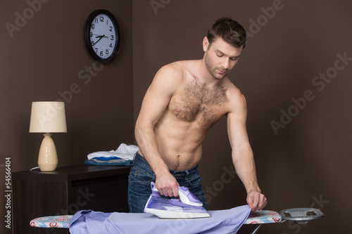 Men ironing. Handsome young men with naked torso ironing his shi
