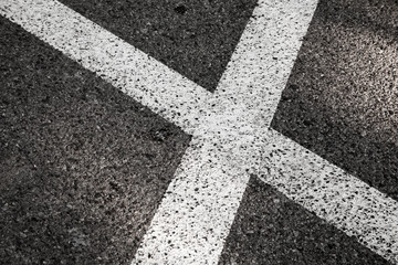 Crossing of white road lines on dark asphalt