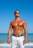 Muscular brutal man on the beach poster