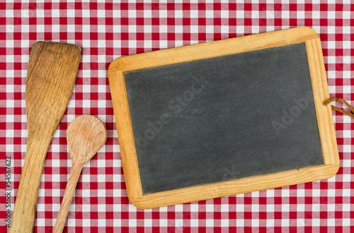 Leere Schiefertafel mit Kochlöffel auf einem Tischtuch