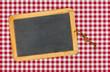 Leere Schiefertafel auf einem rot karierten Tischtuch