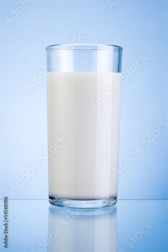 Glass of fresh milk isolated on a blue background