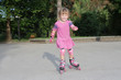 young happy child girl riding roller blades outdoors