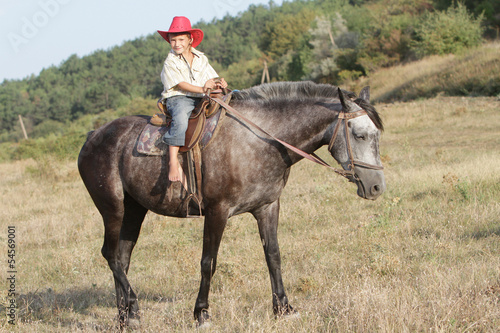 boy riding a horse on farm outdoor portrait
