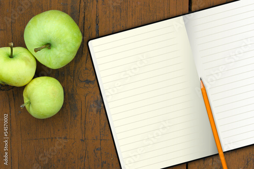 notebook with pencil and apples on a wood table