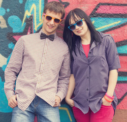 Style teen couple near graffiti background.