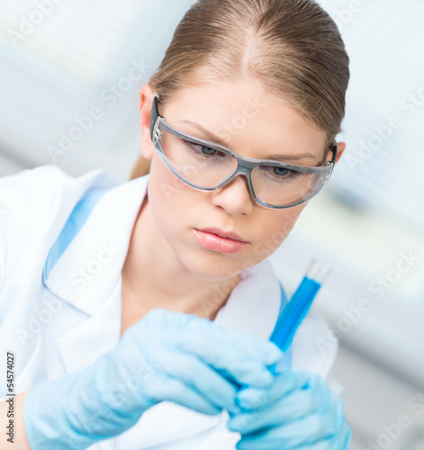 Close-up of technician woman testing liquid sample in laboratory