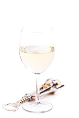 A glass of white wine with a corkscrew