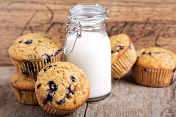 Healthy blueberry banana muffins with milk on a wooden table