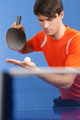 Serving a ball. Confident young men playing table tennis