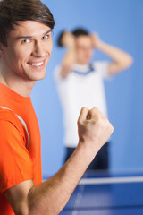 I won! Happy young table tennis player gesturing while his oppon
