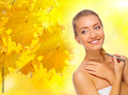 Girl with makeup brush on autumnal background