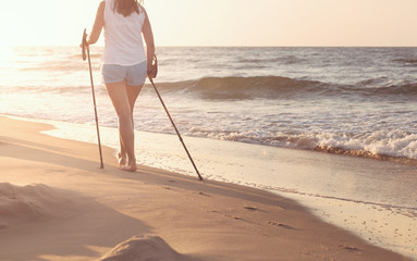 Close up of female nordic walking on a beach