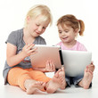 Cute girlfriends sit on the floor and playing with touchpad