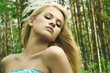 Beautiful blond woman near a tree in a forest