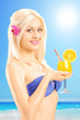 Beautiful blond female in bikini holding a cocktail and posing o