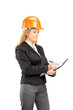 Female architect with a helmet writing on a clipboard