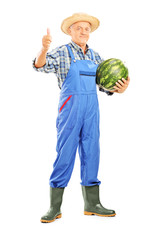 Full length portrait of a smiling farmer holding a watermelon an