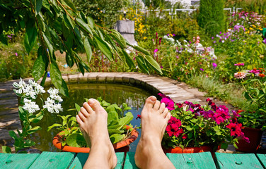 Feet on pool and flowers at cottage. summer Holidays
