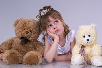 little girl surrounded by plush toys